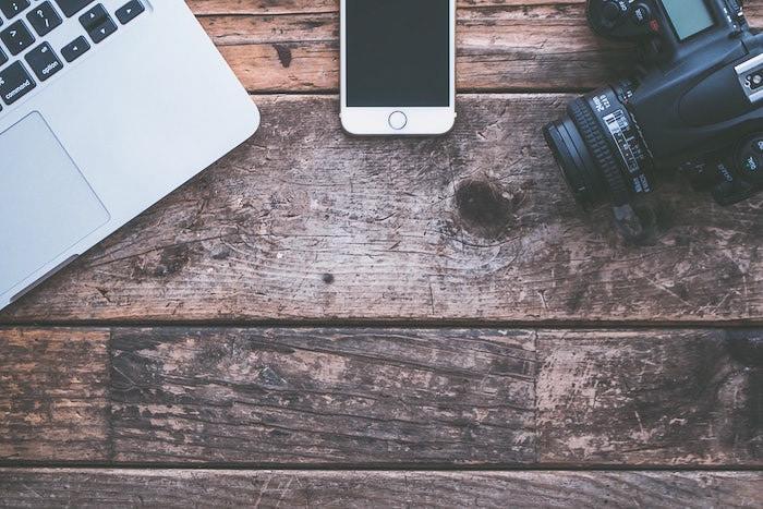 Fotografía cenital del equipo de fotografía en una mesa de madera - consejos de seguros de fotografía