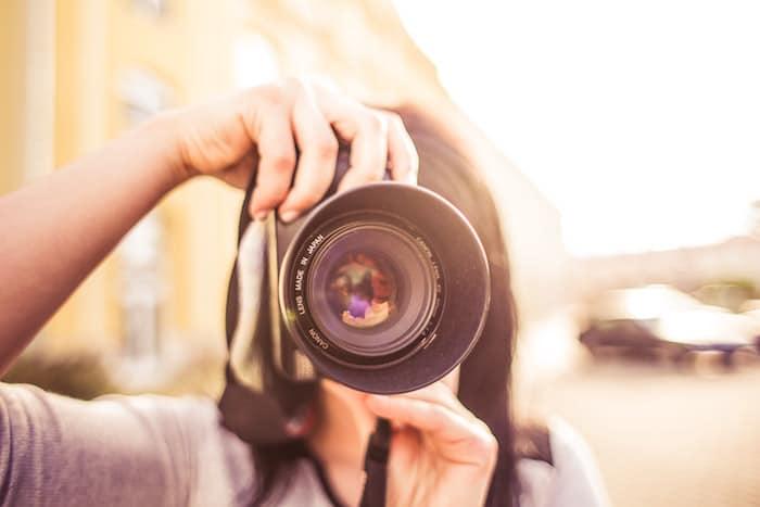 Una niña apuntando una cámara hacia el fotógrafo sobre un fondo borroso suave: consejos para el seguro de fotografía y cámara