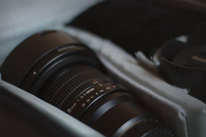 Cerca de la lente de una cámara en su estuche - consejos de seguros de fotografía