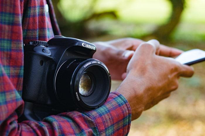 Primer plano de un hombre que sostiene una cámara réflex digital y usa su teléfono inteligente: por qué necesita un seguro de fotografía y un seguro de cámara