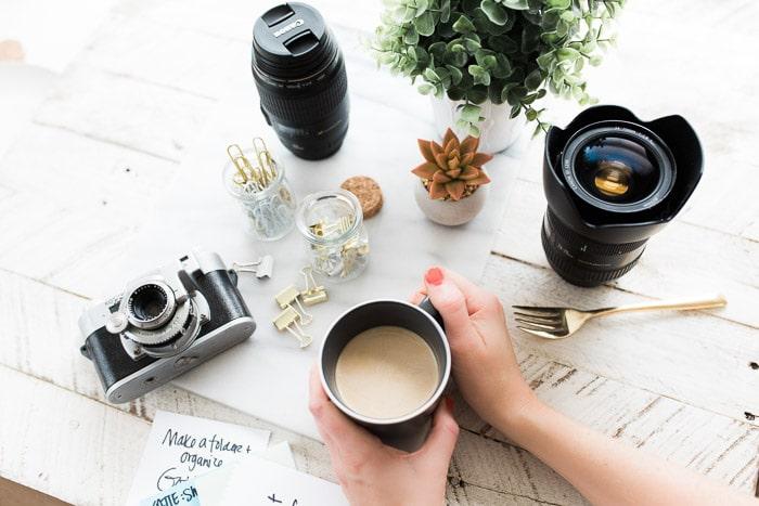 Fotografía cenital de equipo de fotografía, accesorios y taza de café sobre una mesa de madera: consejos para el seguro de la cámara