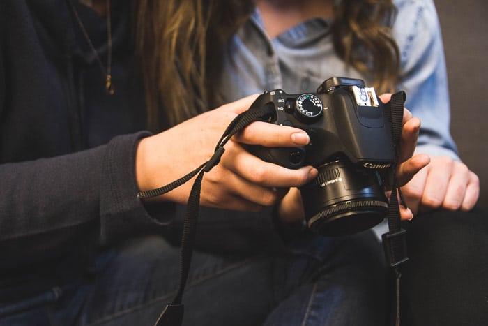 Primer plano de niñas sosteniendo una DSLR y mirando la pantalla: por qué necesita un seguro de fotografía y un seguro de cámara