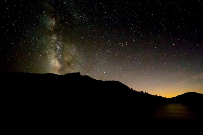 Un impresionante paisaje nocturno debajo de un cielo lleno de estrellas por la noche: tipos de aberraciones de lentes en la fotografía