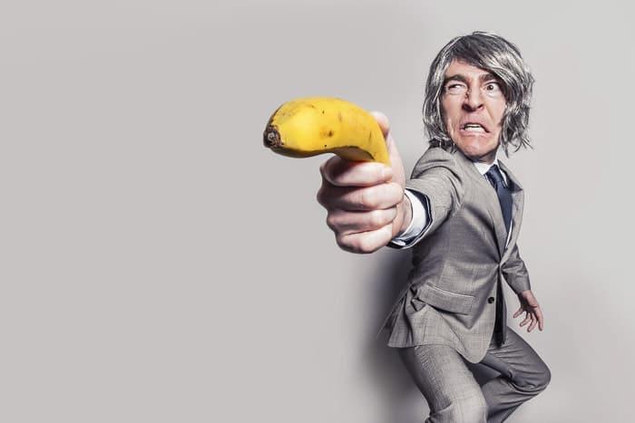 Una foto humorística de un hombre que sostiene un plátano como una pistola, con la forma de su cuerpo distorsionada debido a las aberraciones de la lente.