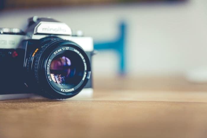 Una cámara en una mesa de madera con un fondo borroso suave: consejos para el seguro de la cámara