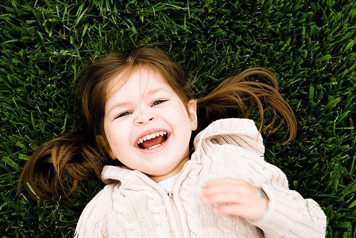 Foto de una niña tendida en la hierba