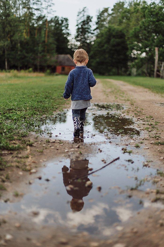Foto de un niño con botas caminando por un camino de tierra