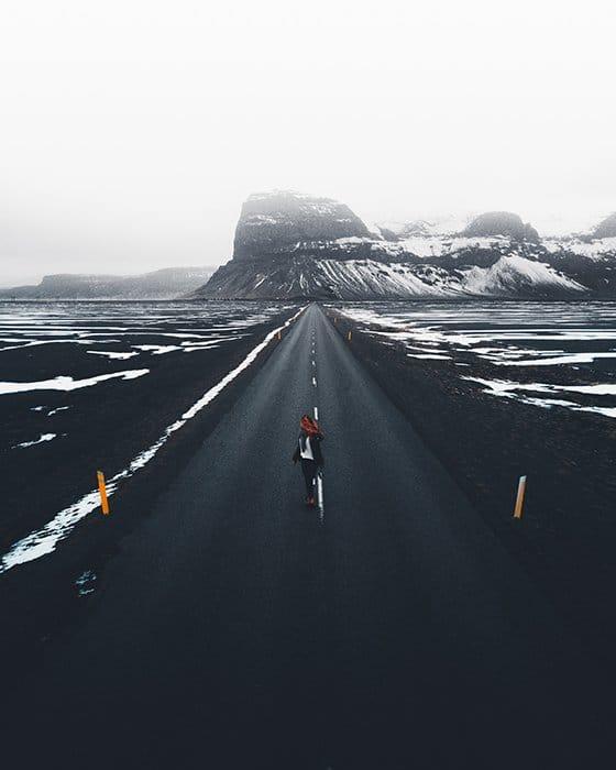 Foto de un largo camino y montañas nevadas con luz tenue
