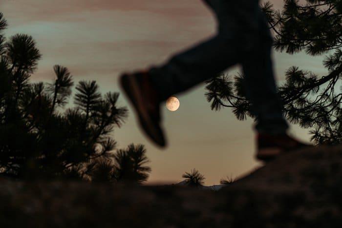 Foto de la silueta de un hombre corriendo con la luna en el fondo