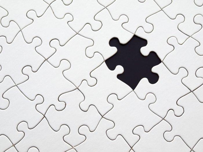 Una imagen de archivo de un rompecabezas blanco con una pieza que falta - imágenes de stock