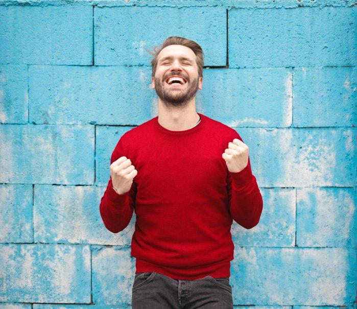 Un retrato de un modelo masculino demasiado feliz posando contra una pared azul - fotos de stock malas