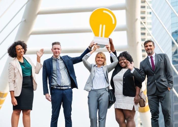 Un retrato de grupo de empleados de la oficina corporativa demasiado felices con una bombilla de cartón - fotos de stock de negocios