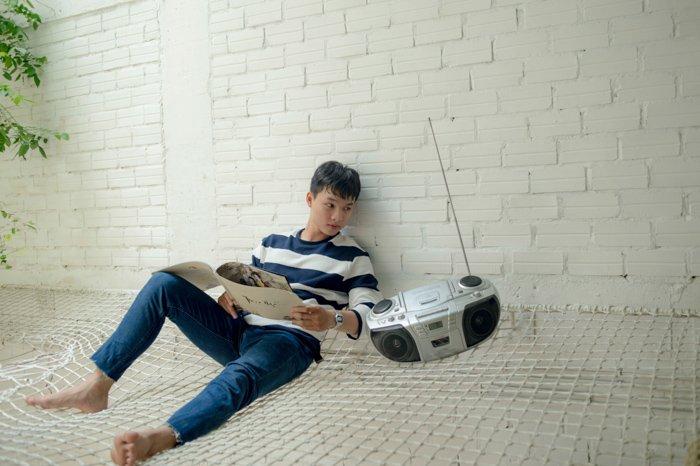 Una foto de archivo mal editada de un hombre sentado junto a una radio