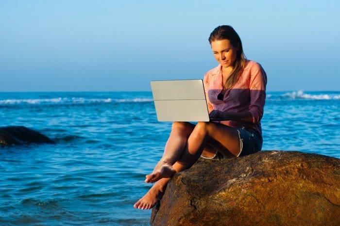 Una niña usando su computadora portátil mientras está sentada sobre una roca en la playa - malas fotos de personas