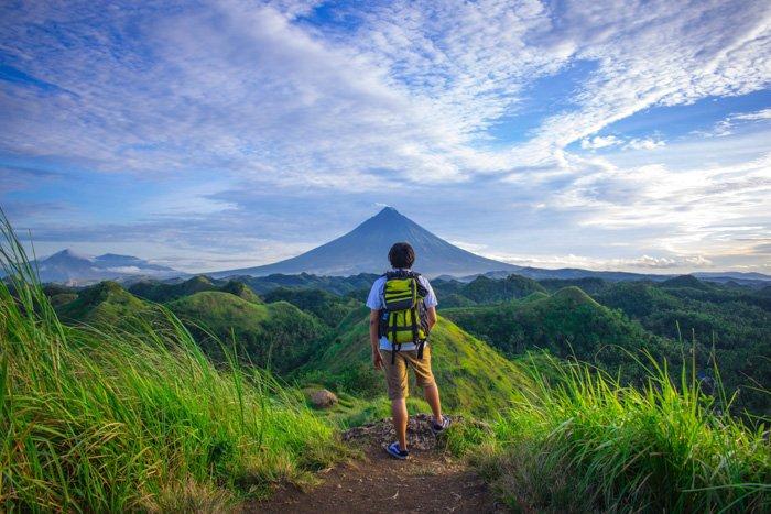 Un retrato de un mochilero contemplando un impresionante paisaje montañoso