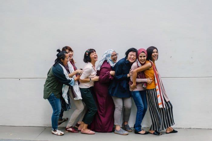 Un retrato común de siete mujeres de pie en una pose de línea de conga - malas fotos de stock