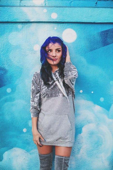 Una fotografía de stock de un modelo femenino de pelo azul posando delante de una pared azul